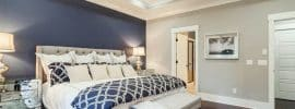 light-gray-bedroom-with-dark-blue-accent-wall-behind-tufted-bed