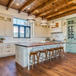 Country kitchen with Bianco Carrara marble counters and exposed beam ceiling