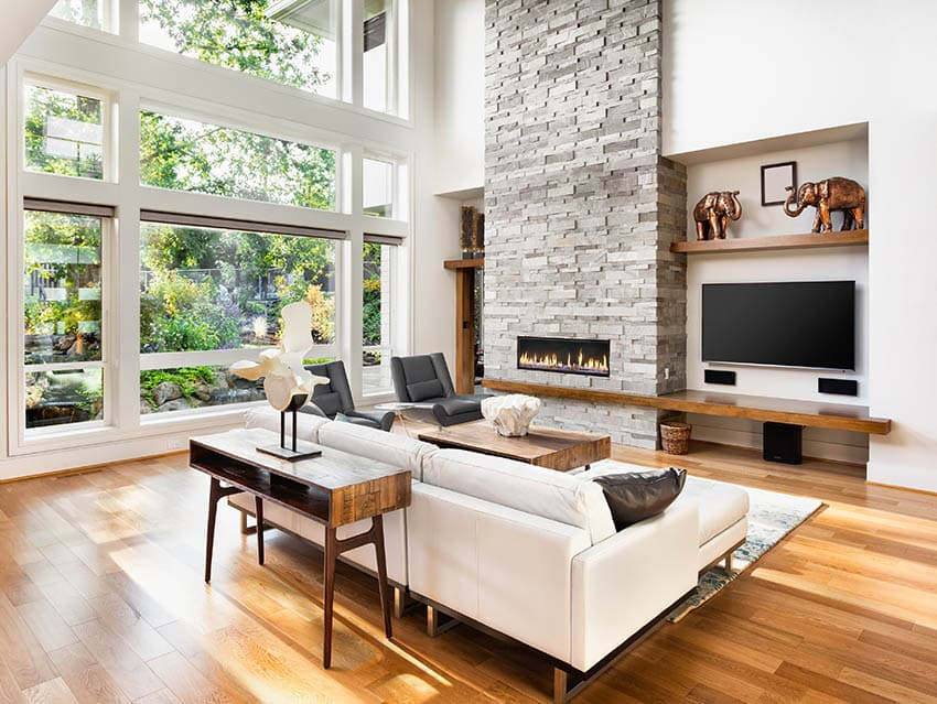 Contemporary living room with high ceiling stone accent fireplace wall niche with built in shelving