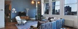 contemporary-living-room-with-navy-blue-accent-wall-wood-flooring-high-ceilings-and-large-window-views