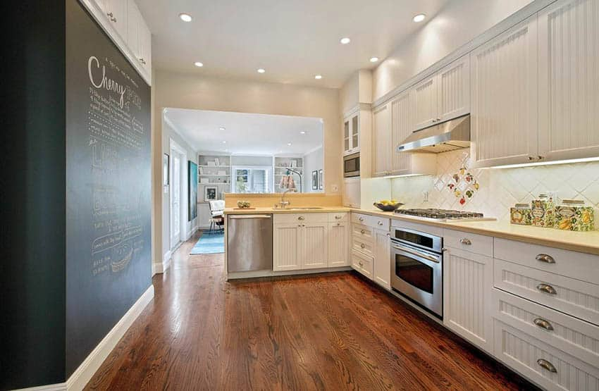 L shaped kitchen with peninsula and white beadboard cabinets