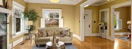 beautiful-living-room-with-gold-semi-gloss-paint-and-white-trim-with-wood-flooring