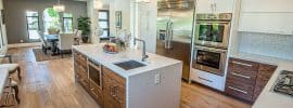 contemporary-kitchen-with-two-tone-brown-and-white-cabinets-and-synthetic-quartz waterfall-island