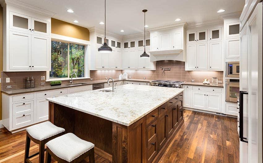Kitchen with white granite countertop island gray quartz countertops white cabinets wood flooring