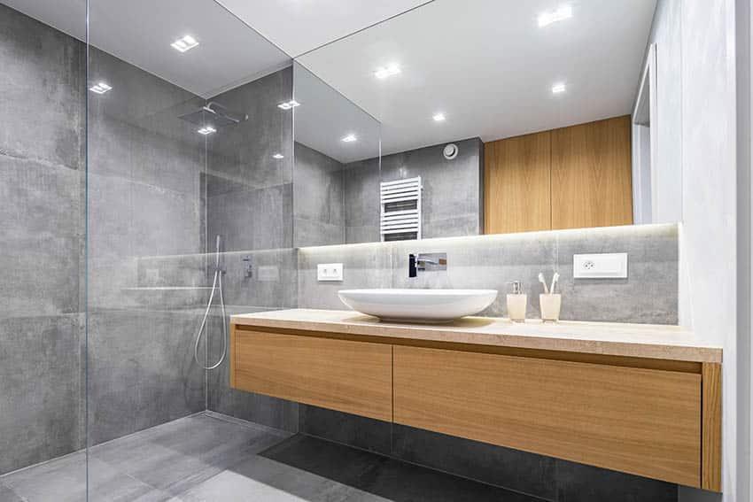Modern bathroom with concrete countertop floating vanity vessel sink glass shower enclosure
