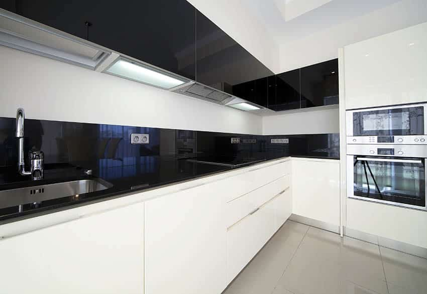 Modern galley kitchen with black quartz countertops and white cabinets