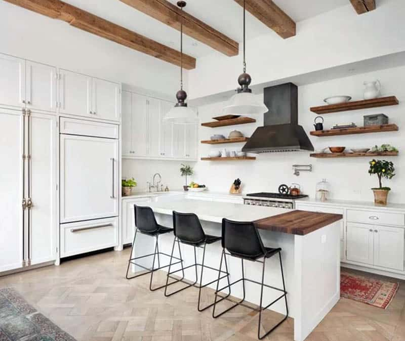 Country style kitchen with l shape and island with butcher block open shelving and wood beams