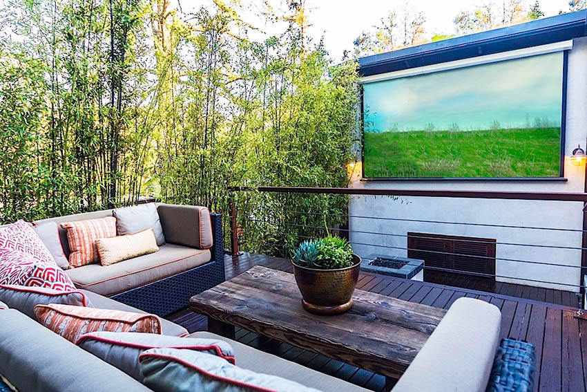 Elevated wood deck with outdoor furniture and projection screen