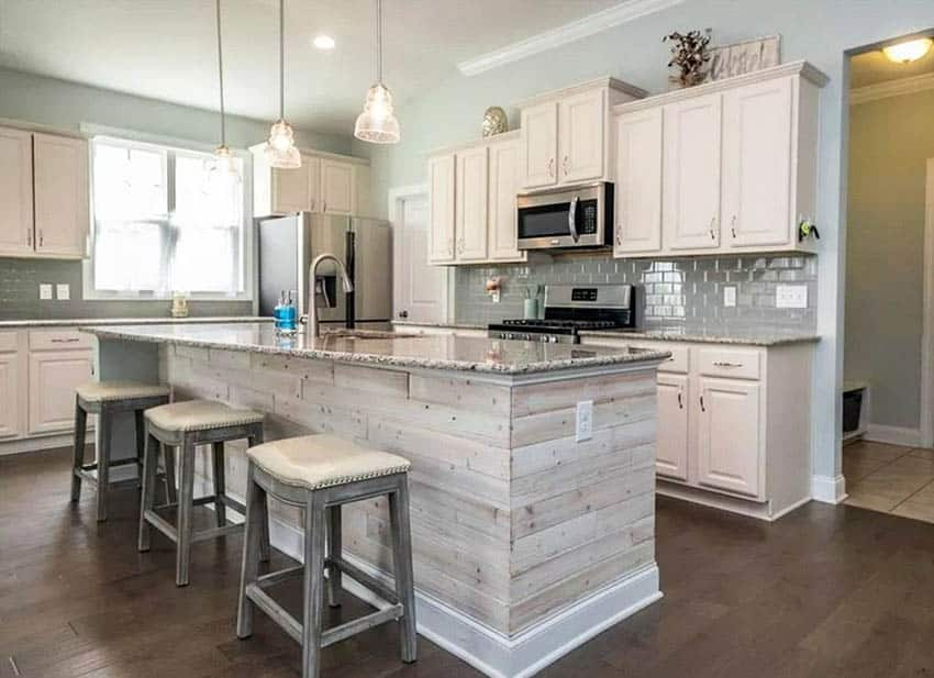 L shaped country kitchen with wood plank island and granite countertops