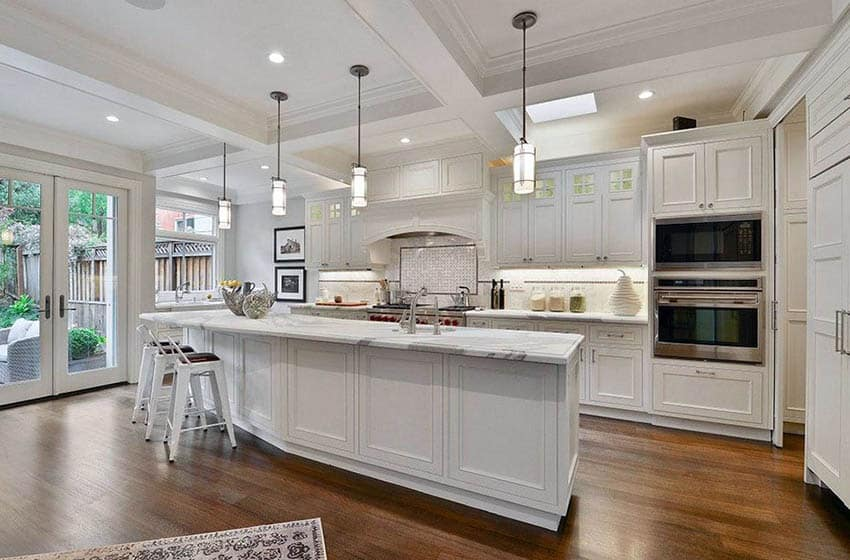 L shaped kitchen with angled island marble countertops and white cabinets