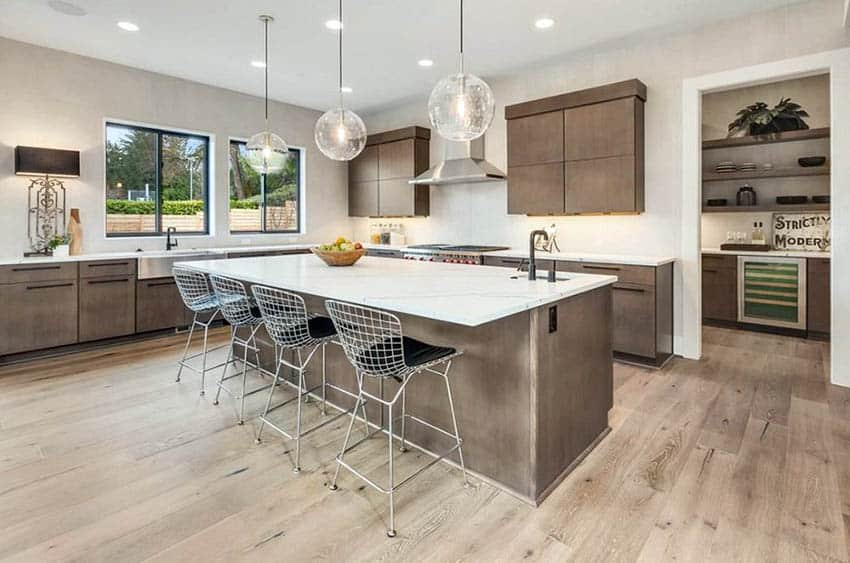 Modern kitchen with l shape island and pantry area with more cabinets
