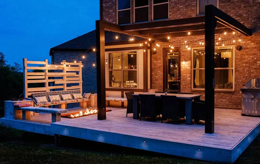 Wood deck with pergola, sunken fire pit, hanging lights and outdoor dining table