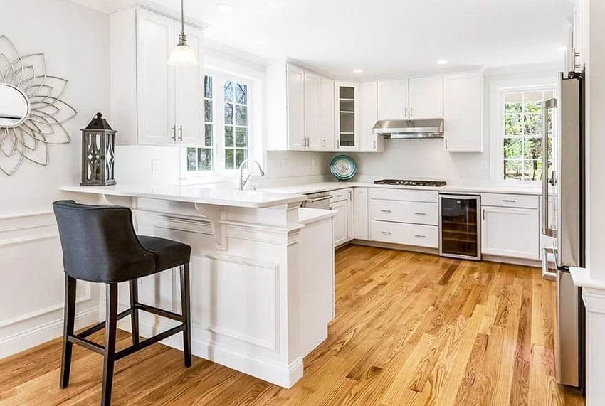 Kitchen with white cabinets small breakfast bar peninsula wood flooring