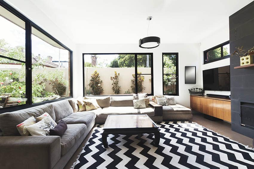 Contemporary living room with bold area rug gas fireplace black accent tile black framed windows