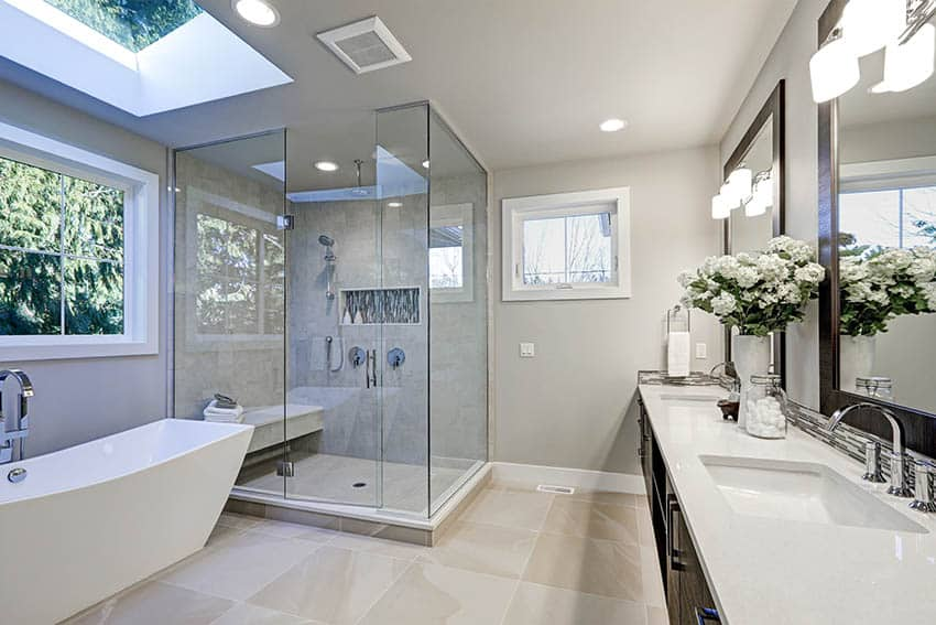 Master bathroom with dark wood vanity, arctic white quartz countertop and freestanding tub