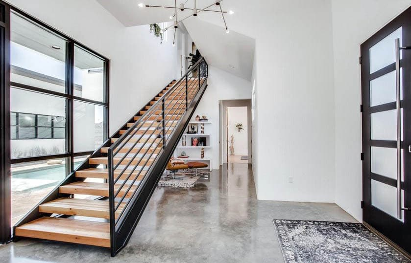 Contemporary entryway with metal stair railing with wood steps and concrete flooring