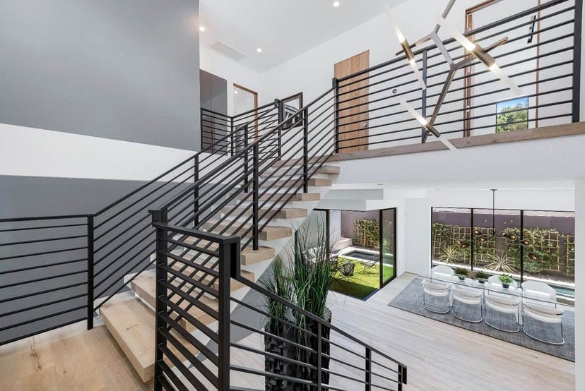 Contemporary home with metal stair railing and light wood flooring