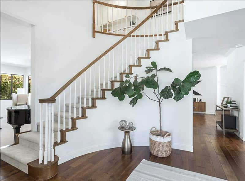 Home entry with white painted stair railing and wood flooring