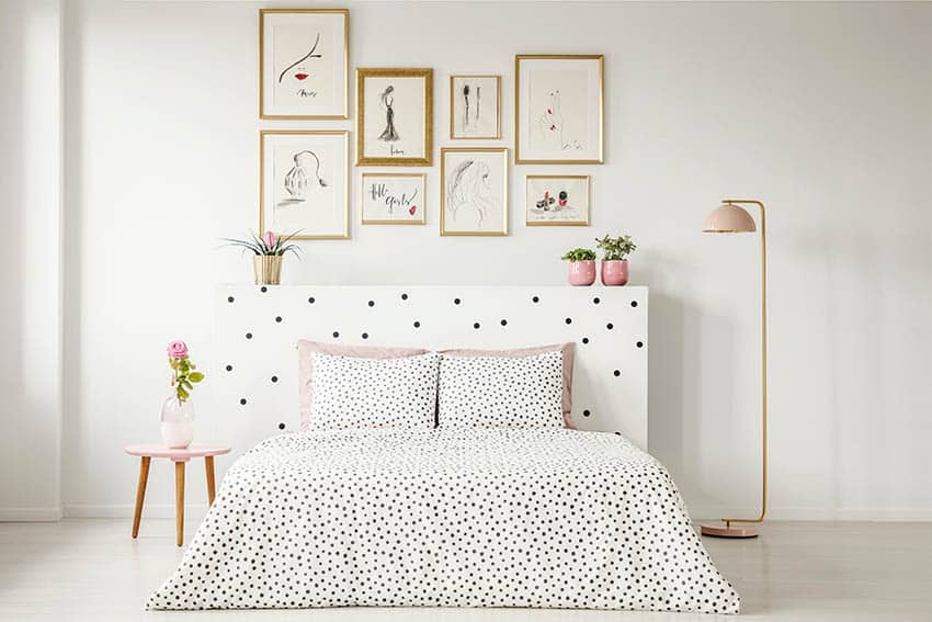 White bedroom with black and white patterned bed spread pictures on wall