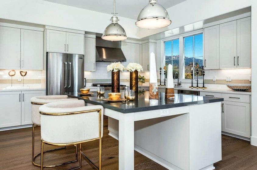 Contemporary kitchen with white cabinets dark quartz countertop island