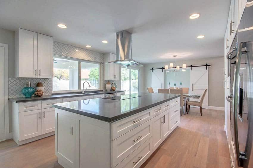 Contemporary kitchen with white cabinets gray quartz countertops center island arabesque backsplash tile