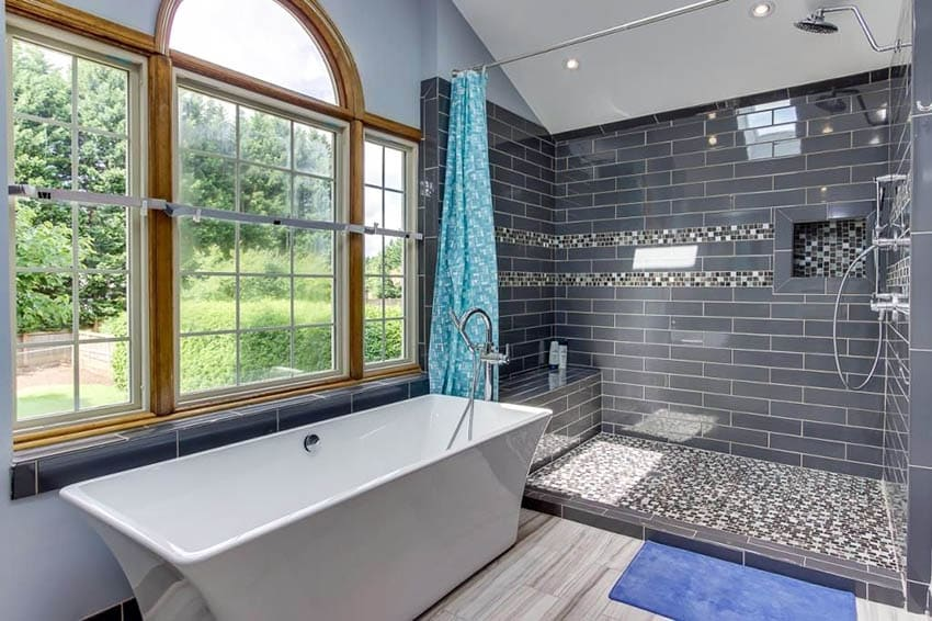 Contemporary master bathroom with glass tile shower and bench with freestanding tub