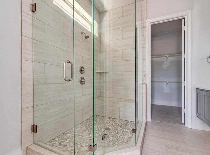 Glass shower with porcelain tile bench river rock floor
