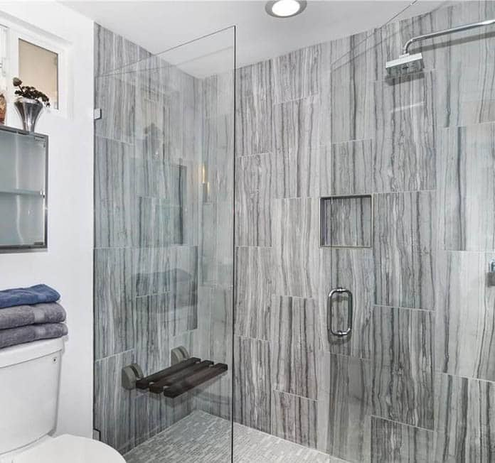 Guest bathroom with porcelain tile shower and folding bench