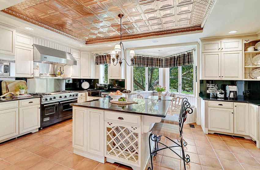Kitchen with antique white cabinets and black granite countertops with copper tray ceiling
