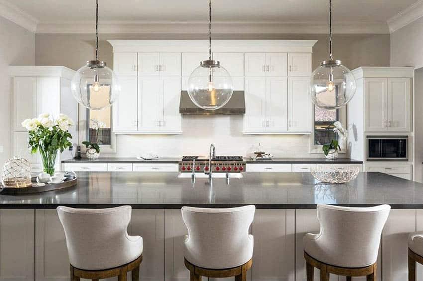 Kitchen with white cabinets and black quartz countertops globe pendant lights over island