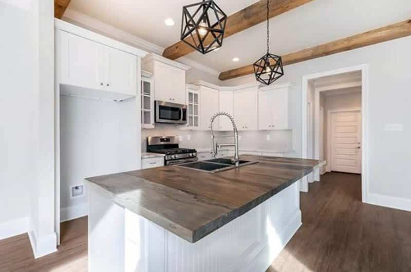 Kitchen with white cabinets beadboard island and wood countertops