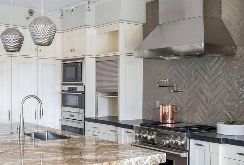 Kitchen with white cabinets brown quartz countertop island and black soapstone countertops
