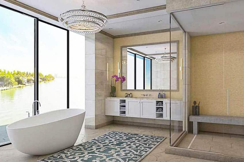 Luxury modern bathroom with glass shower and stone bench tub water views