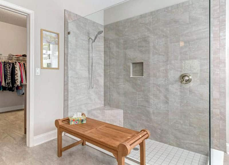 Master bathroom with tile shower corner bench and portable wood bench