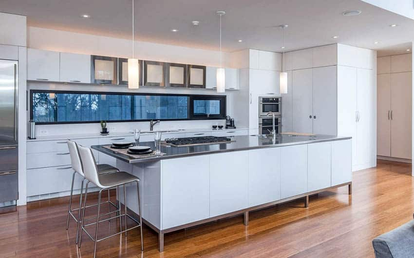 Modern kitchen with white cabinets and stainless steel countertop island
