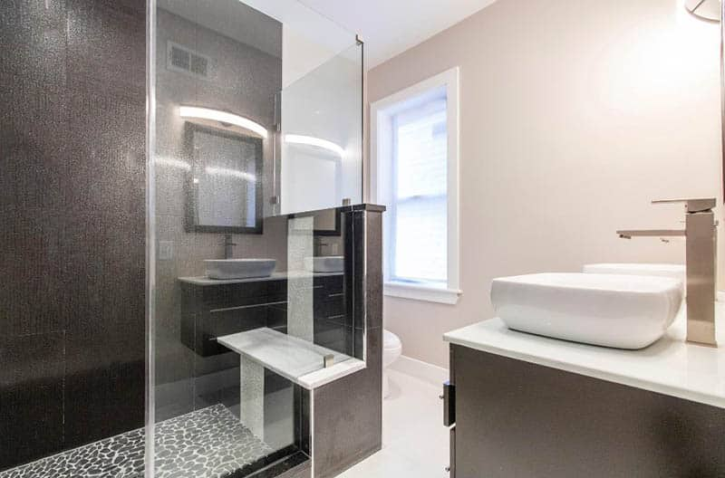 Modern shower with white tile bench and black tile walls