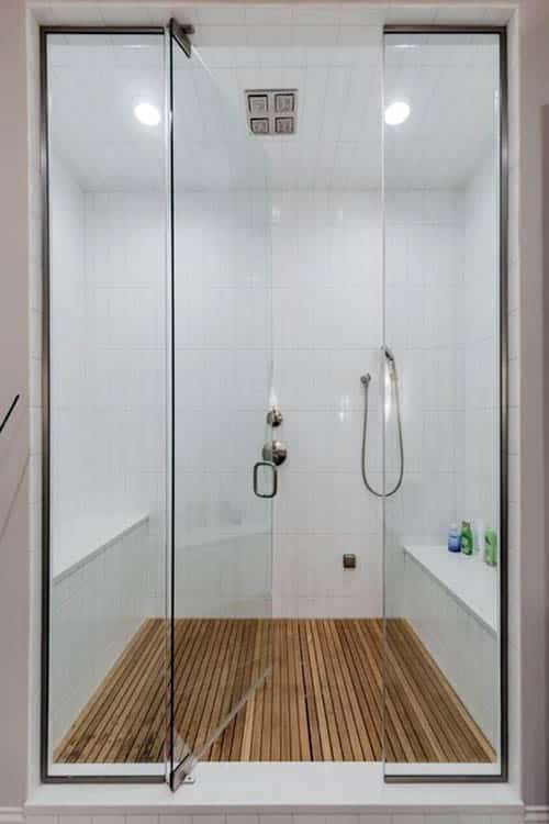 Walk in tile shower with two benches and teak floor