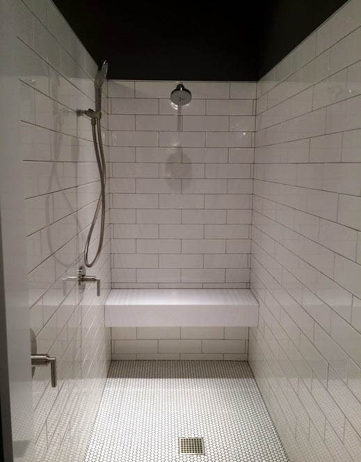 White tile shower with floating bench and penny tile flooring