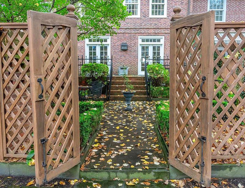 Diamond lattice fence with gate to house