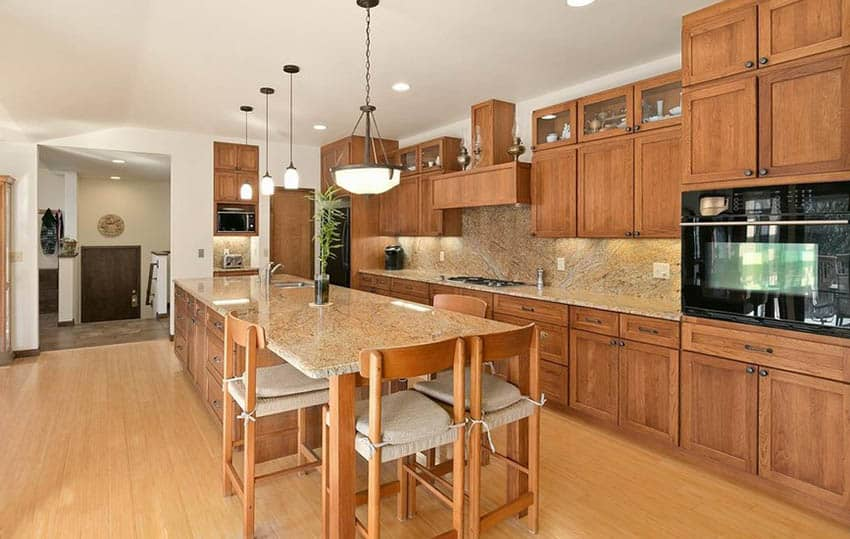 Kitchen with bamboo flooring, wood cabinets and beige granite countertops
