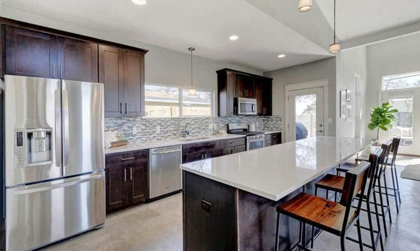 Kitchen with concrete flooring, brown cabinets and white quartz countertop