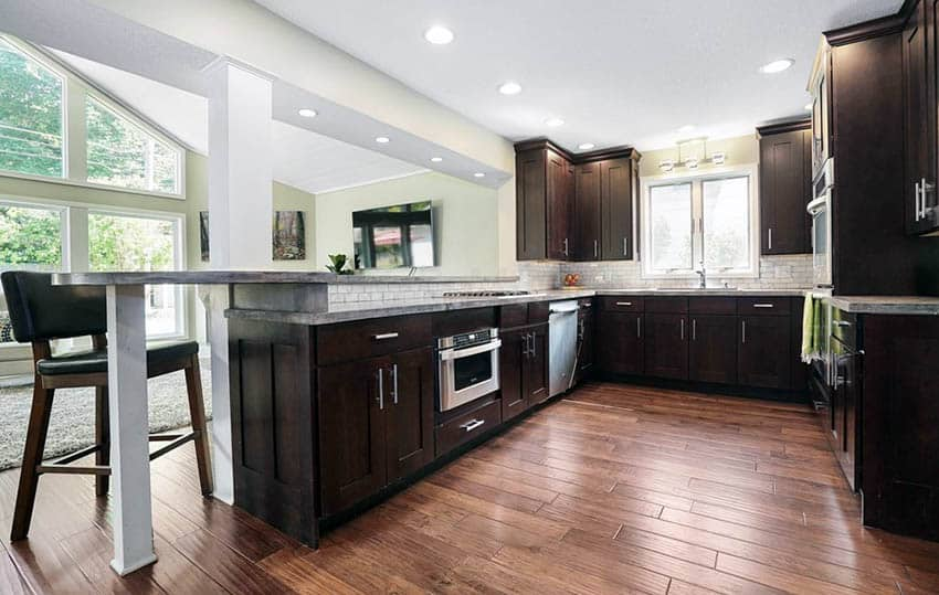 Kitchen with cork flooring and dark cabinets with breakfast bar peninsula