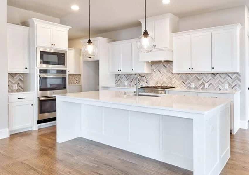 Kitchen with hardwood floor white cabinets and white quartz countertops