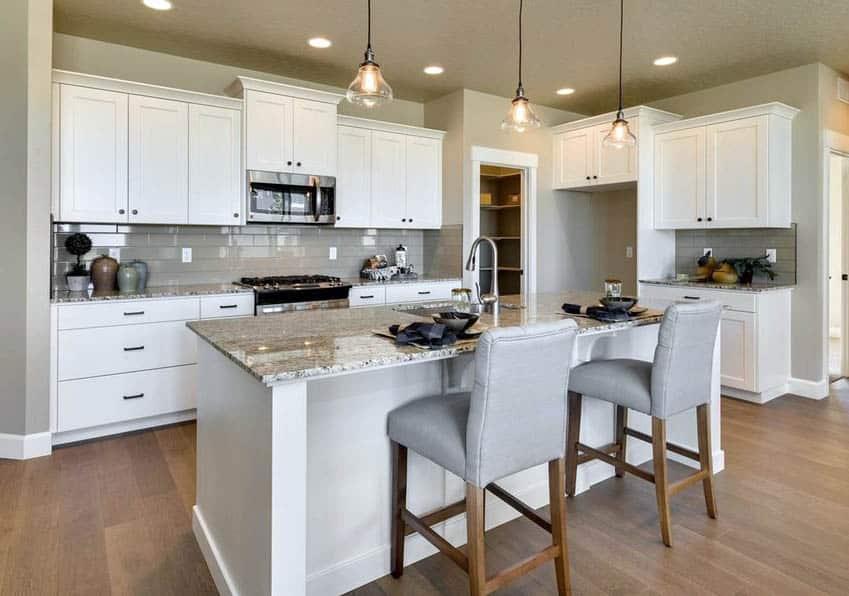 Kitchen with hardwood flooring, white cabinets, granite countertops and porcelain tile backsplash