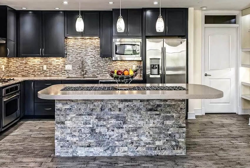 Kitchen with stacked stone island and dark cabinets