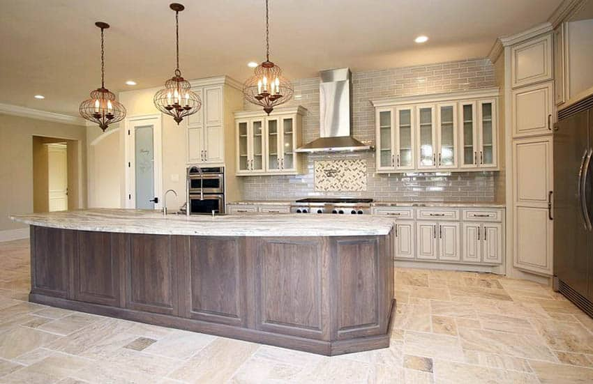 Open kitchen with travertine flooring, off white cabinets and wood island