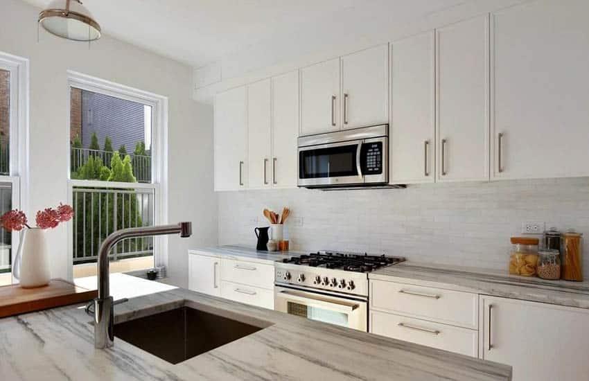 Kitchen with carrara marble subway tile backsplash