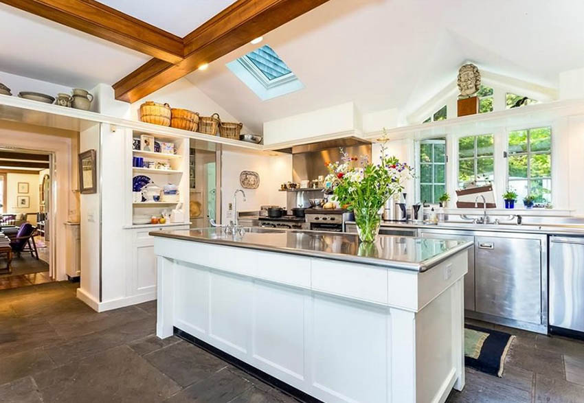 Country kitchen with stainless steel countertops with bullnose edge and white cabinets