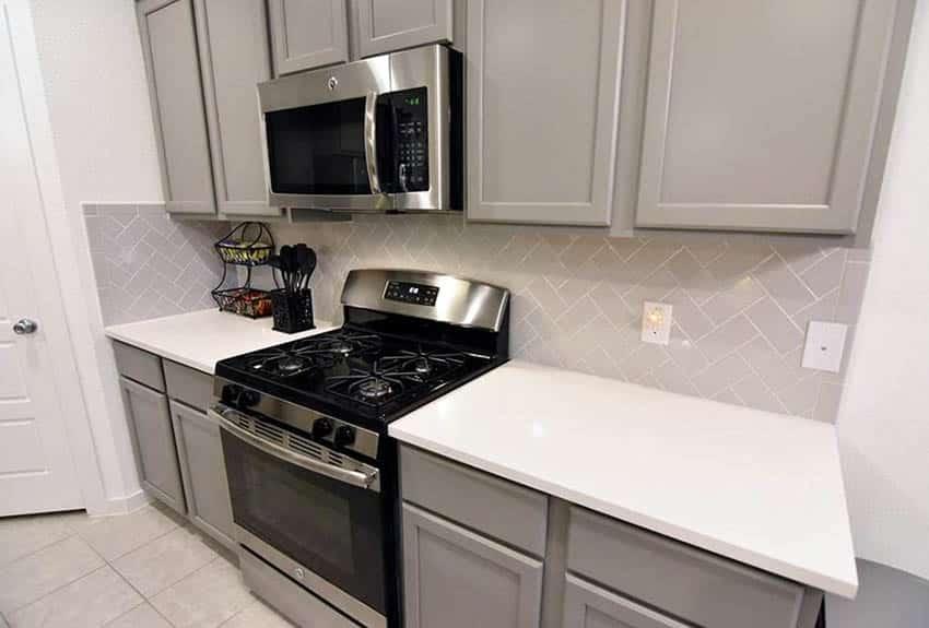 Kitchen with diagonal herringbone pattern subway tile backsplash
