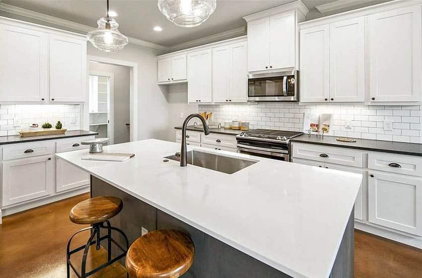 Kitchen with porcelain subway tile backsplash quartz countertops and white cabinets